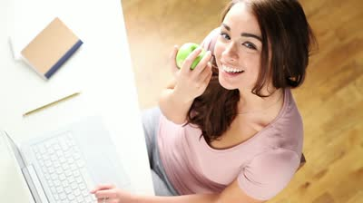stock-footage-pretty-young-university-student-is-keeping-healthy-eating-a-green-apple-while-studying-at-home